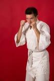 Homem novo na arte marcial branca do treinamento do quimono imagem de stock royalty free