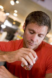 Homem novo na barra que olha fixamente forlornly em uma bebida Imagens de Stock Royalty Free