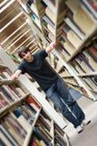 Homem novo na biblioteca Fotos de Stock Royalty Free