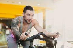 Homem novo na bicicleta dos artigos de papelaria do passeio do gym Fotos de Stock