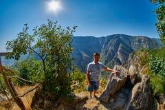 Homem novo na borda do desfiladeiro da montanha Imagens de Stock Royalty Free