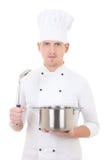 Homem novo na caçarola uniforme e na colher guardando do cozinheiro chefe isoladas sobre Fotografia de Stock