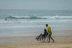 Homem novo na cadeira de rodas e seu frend na estrada à praia surf imagem de stock royalty free
