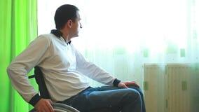 Homem novo na cadeira de rodas que olha fora filme