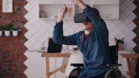 Homem novo na cadeira de rodas usando o capacete da realidade virtual em casa filme