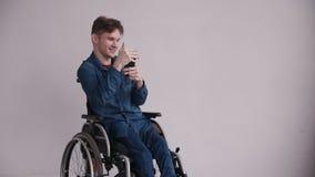 Homem novo na cadeira de rodas usando o smartphone moderno em casa video estoque
