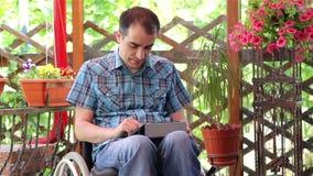 Homem novo na cadeira de rodas usando um tablet pc filme