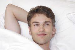 Homem novo na cama imagem de stock royalty free