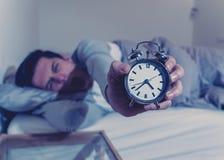 Homem novo na cama com o sentimento do despertador desesperado e a aflição não capaz de dormir com insônia imagem de stock royalty free