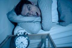 Homem novo na cama com o sentimento do despertador desesperado e a aflição não capaz de dormir com insônia fotos de stock