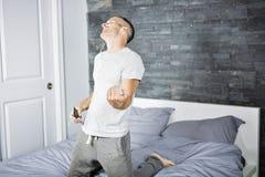 Homem novo na cama que joga Air Guitar Imagens de Stock