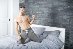 Homem novo na cama que joga Air Guitar Imagem de Stock