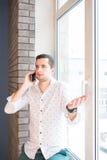 Homem novo na camisa branca que fala sobre o telefone com a expressão interrogativa foto de stock royalty free