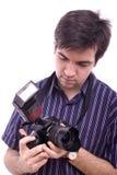 Homem novo na camisa com uma câmera moderna da foto de SLR Imagens de Stock