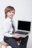 Homem novo na camisa e laço que senta-se com um portátil imagem de stock royalty free