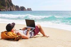 Homem novo na camiseta de alças, no short, no tampão do snapback na praia com portátil & na trouxa Freelancer, blogger do moderno imagens de stock royalty free