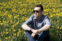 Homem novo na cena da mola com narcisos amarelos Imagem de Stock