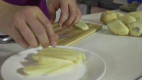 Homem novo na cozinha que corta as batatas com uma faca na placa de corte na cozinha filme
