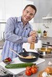 Homem novo na cozinha que cozinha ovos fritos Foto de Stock