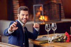 Homem novo na data no restaurante que senta-se com ramalhete que aponta na câmera alegre imagem de stock royalty free