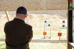 Homem novo na escala de tiro da pistola Fotografia de Stock