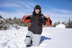 Homem novo na floresta do inverno, apreciando a neve do inverno Imagens de Stock