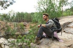 Homem novo na montanha rochosa perto da floresta imagens de stock royalty free