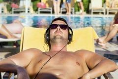 Homem novo na música de escuta da praia com um smartphone Fotos de Stock Royalty Free