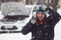 Homem novo na neve, está sob o esforço porque seu Ca dividido imagem de stock