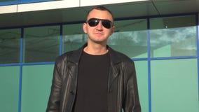 Homem novo na posição do casaco de cabedal e dos óculos de sol exterior filme