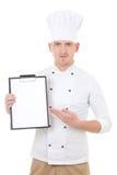 Homem novo na prancheta mostrando uniforme do cozinheiro chefe com o isolador do espaço da cópia Foto de Stock