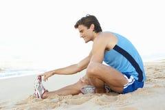 Homem novo na roupa da aptidão que estica na praia Fotografia de Stock