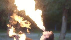 Homem novo na roupa preta que executa uma mostra com a posição da chama no riverbank Expiração hábil do artista do fireshow vídeos de arquivo