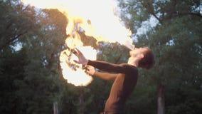 Homem novo na roupa preta que executa uma mostra com a posição da chama no riverbank Expiração hábil do artista do fireshow video estoque