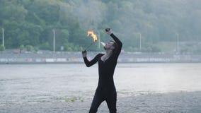 Homem novo na roupa preta que executa uma mostra com a posição da chama no riverbank Expiração hábil do artista do fireshow filme