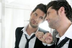 Homem novo narcisístico considerável em um espelho Foto de Stock