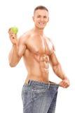 Homem novo nas calças de brim desproporcionados que guardam uma maçã Fotografia de Stock Royalty Free