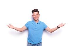 Homem novo nas calças de brim e no acolhimento azul do polo Fotografia de Stock