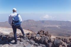 Homem novo no auge da montanha que olha afastado imagens de stock royalty free