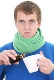 Homem novo no azul com medicina e copo Fotografia de Stock Royalty Free