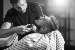 Homem novo no barbeiro Fotografia de Stock Royalty Free