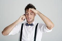Homem novo no bowtie no telefone e no frus Imagem de Stock