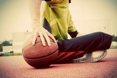 Homem novo no campo de básquete Assento e pingar com bola Fotografia de Stock