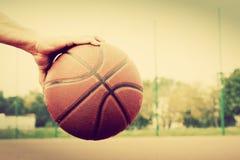 Homem novo no campo de básquete Pingar com bola Fotografia de Stock Royalty Free