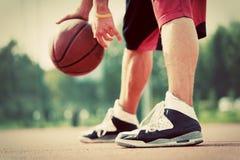 Homem novo no campo de básquete que pinga com bola Fotografia de Stock