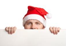 Homem novo no chapéu de Santa que prende um sinal em branco Fotografia de Stock