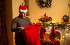 Homem novo no chapéu vermelho que olha dentro do saco de Santa com perplexidade Fotos de Stock Royalty Free