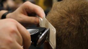 Homem novo no conceito de Barber Shop Hair Care Service Equipe as mãos do ` s que fazem um corte de cabelo para o homem na barbea imagem de stock royalty free
