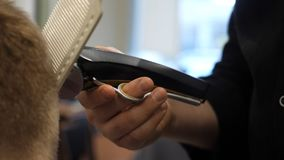 Homem novo no conceito de Barber Shop Hair Care Service Equipe as mãos do ` s que fazem um corte de cabelo para o homem na barbea imagem de stock