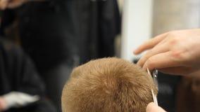 Homem novo no conceito de Barber Shop Hair Care Service Equipe as mãos do ` s que fazem um corte de cabelo para o homem na barbea foto de stock